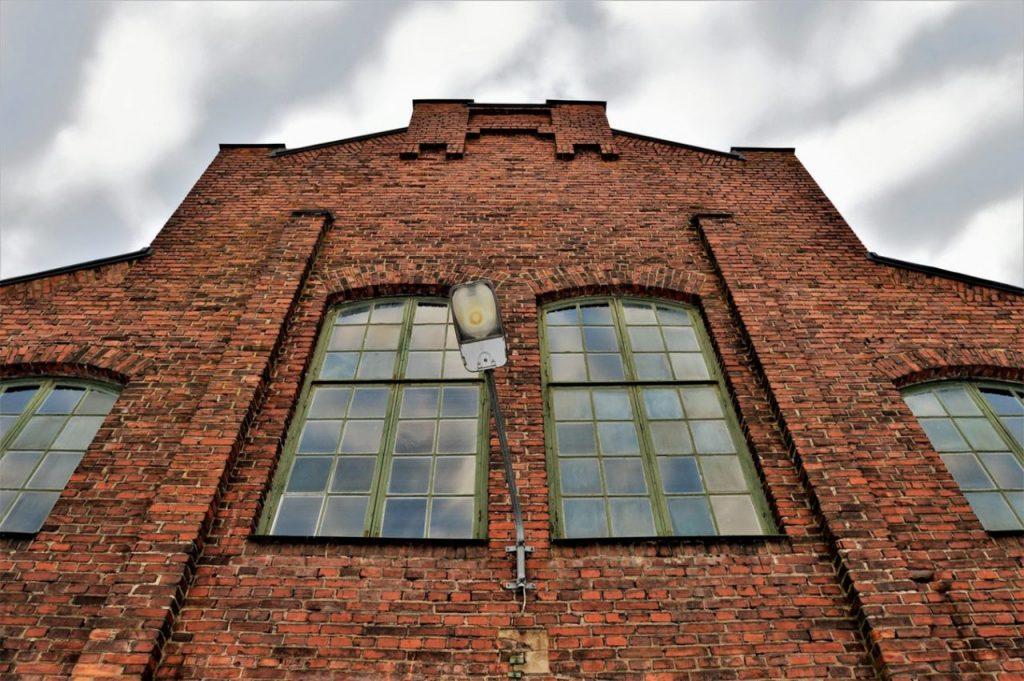 Tegelhus med rött tegel, lampa och stora industrifönster